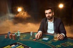 坐在啤牌桌上的西装的一个年轻人 人赌博 赌桌纸牌的球员 免版税库存图片