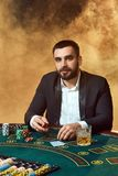 坐在啤牌桌上的西装的一个年轻人 人赌博 赌桌纸牌的球员 免版税图库摄影