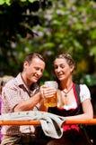 坐在啤酒庭院里的愉快的夫妇 库存图片