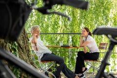 坐在啤酒庭院里的更加年轻和更老的女商人 免版税图库摄影
