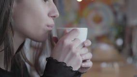 坐在喝她的从白色杯子的现代咖啡馆的桌上的年轻女人接近的画象茶 俏丽的夫人享用 股票视频