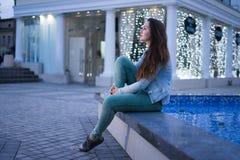 坐在喷泉附近和看在夜城市的单独美丽的女孩 免版税库存图片