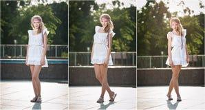 坐在喷泉附近的白色短的礼服的可爱的女孩在夏天最热的天 图库摄影