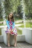 坐在喷泉附近的逗人喜爱的小女孩 走 免版税库存照片