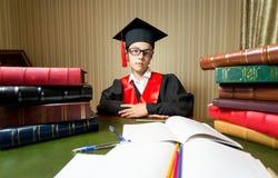 坐在图书馆的毕业盖帽和黑褂子的女孩 免版税库存照片
