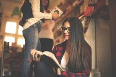 坐在图书馆阅读书的女学生女孩 库存照片
