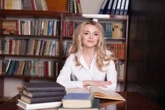 坐在图书馆阅读书的女孩为检查做准备 图库摄影