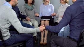 坐在圈子和握手的上瘾的人民在疗期,支持 免版税库存图片