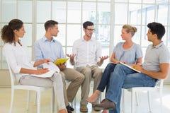 坐在圈子的偶然企业队开会议 库存照片