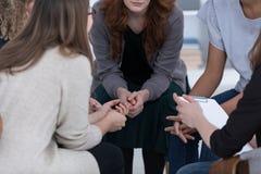 坐在圈子的匿名妇女在小组聚会期间 免版税库存图片