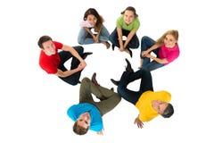 坐在圈子的小组不同种族的朋友 免版税库存图片