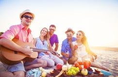 坐在圈子的海滩的朋友 一个人演奏guita 免版税库存照片