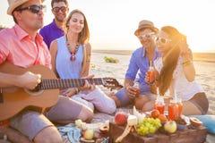 坐在圈子的海滩的朋友 一个人演奏guita 免版税图库摄影