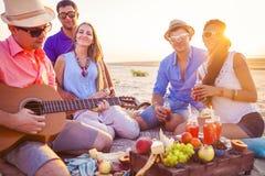 坐在圈子的海滩的朋友 一个人演奏guita 库存照片