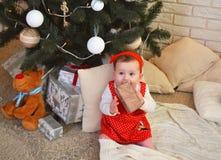 坐在圣诞树下和在她的手上的逗人喜爱的小女孩拿着一件礼物 库存图片