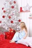 坐在圣诞树下和寻找礼物的小女孩 免版税库存图片