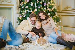 坐在圣诞树下的一个年轻家庭 库存照片