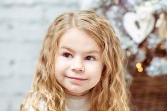 坐在圣诞树下的可爱的白肤金发的小女孩 免版税库存图片