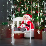 坐在圣诞树下的圣诞老人服装和帽子的逗人喜爱的新出生的婴孩 免版税库存照片
