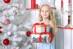 坐在圣诞树下的小女孩 库存照片