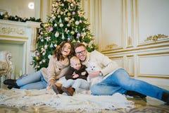 坐在圣诞树下的愉快的家庭 免版税图库摄影