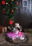 坐在圣诞树下的逗人喜爱的小女孩 使用与玩具火车的孩子 图库摄影