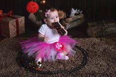 坐在圣诞树下的逗人喜爱的小女孩 婴孩在她的手上的拿着一列玩具火车 库存图片