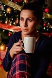 坐在圣诞树前面和拿着杯子的女孩 免版税库存图片