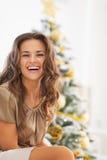 坐在圣诞树前面的微笑的少妇 免版税库存照片