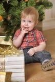 坐在圣诞树和礼物旁边的男孩 免版税图库摄影
