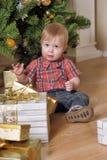 坐在圣诞树和礼物旁边的男孩 库存图片