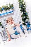 坐在圣诞树和Christma旁边的小俏丽的女孩 库存图片