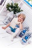 坐在圣诞树和Christma旁边的小俏丽的女孩 免版税库存照片