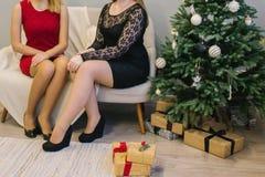 坐在圣诞树开头旁边的两个美丽的女孩出席 两个女孩在树和礼物旁边坐 免版税库存图片