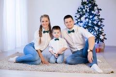 坐在圣诞树新年礼物假日冬天的人妇女和年轻儿子 免版税库存照片