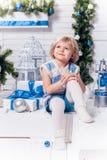 坐在圣诞树旁边的小微笑的俏丽的女孩和 库存图片