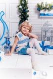 坐在圣诞树旁边的小微笑的俏丽的女孩和 库存照片
