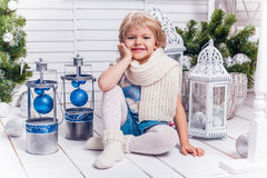 坐在圣诞树旁边的小微笑的俏丽的女孩和 免版税库存照片