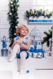 坐在圣诞树旁边的小微笑的俏丽的女孩 库存图片