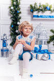 坐在圣诞树旁边的小微笑的俏丽的女孩 免版税库存图片