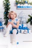 坐在圣诞树旁边的小微笑的俏丽的女孩 免版税图库摄影