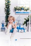 坐在圣诞树旁边的小微笑的俏丽的女孩 图库摄影