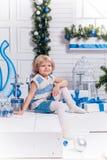 坐在圣诞树旁边的小微笑的俏丽的女孩 库存照片