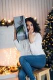 坐在圣诞树旁边的白色毛线衣的惊奇的美丽的性感的少妇,拿着礼物 婴孩圣诞节克劳斯帽子演奏s圣诞老人的母亲照片一起佩带 库存图片