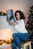 坐在圣诞树旁边的白色毛线衣的惊奇的美丽的性感的少妇,拿着礼物 婴孩圣诞节克劳斯帽子演奏s圣诞老人的母亲照片一起佩带 图库摄影