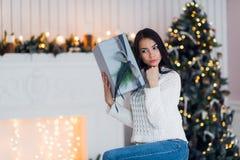 坐在圣诞树旁边的白色毛线衣的惊奇的美丽的性感的少妇,拿着礼物 婴孩圣诞节克劳斯帽子演奏s圣诞老人的母亲照片一起佩带 免版税库存图片