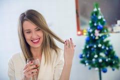 坐在圣诞树旁边的美丽的妇女享用玻璃  库存图片