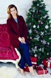坐在圣诞树的愉快的中间妇女画象  免版税库存照片