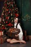 坐在圣诞树的毛线衣的美丽的女孩 礼物,新年 免版税库存照片