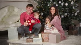 坐在圣诞树附近和在他的手上的友好的家庭拿着孟加拉光 股票视频